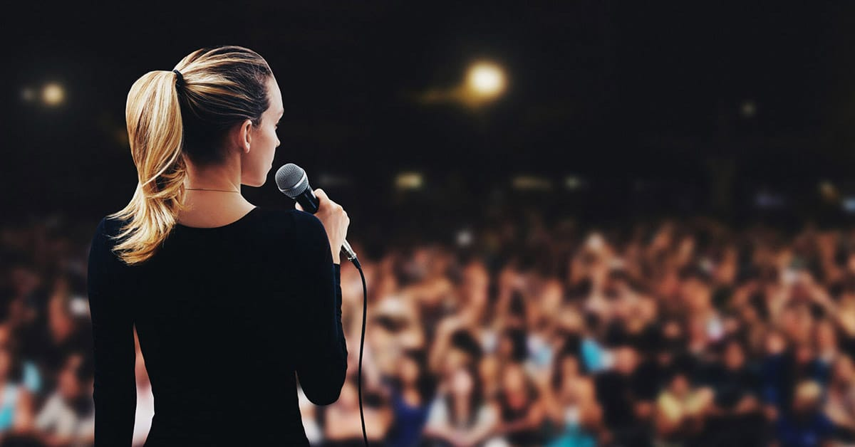 woman speaking on stage in front of large audience